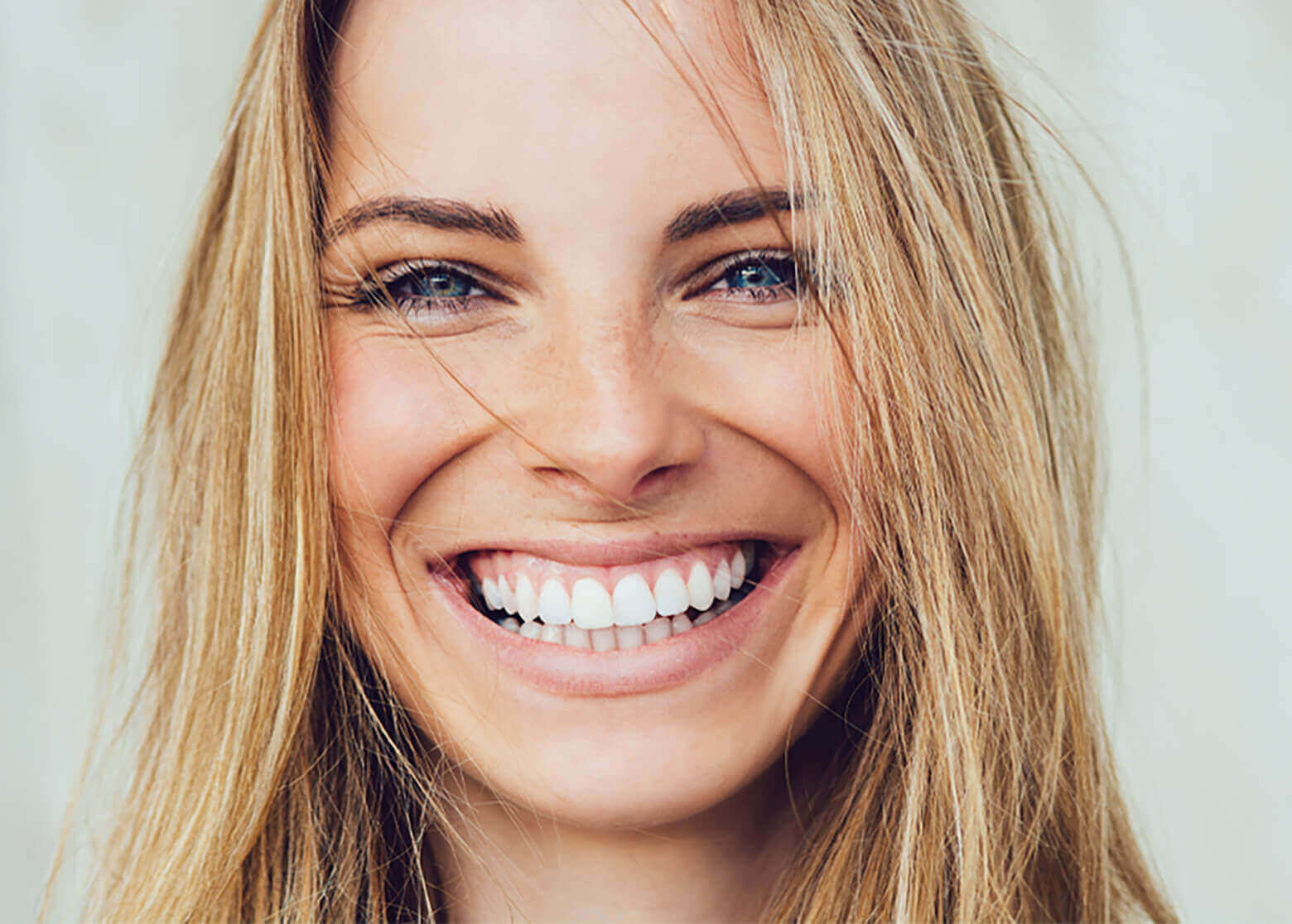 Blonde woman with white teeth smiling.