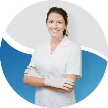 Female dentist wearing all white and smiling with her arms folded