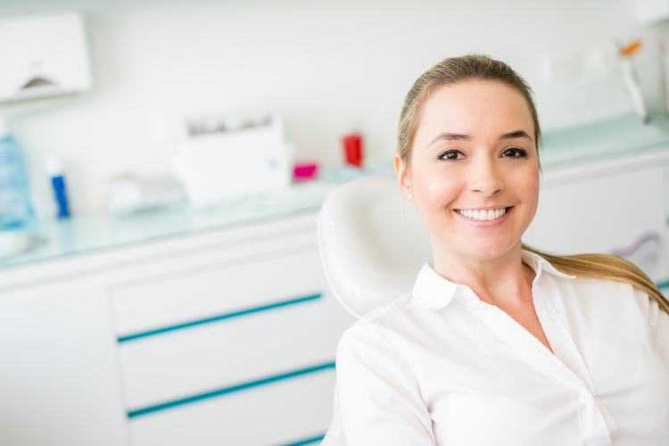 Smiling young woman in dental chair with smooth skin and hair pulled back