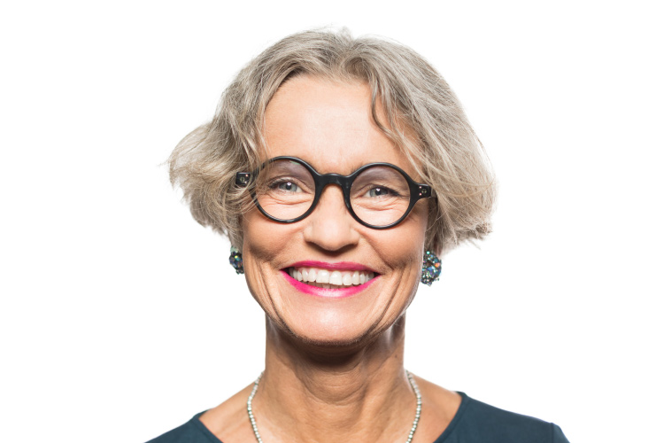 Smiling older woman with nice skin, round glasses and red lipstick