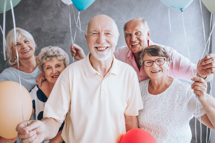 Four smiling mature men and women holding balloons gathered around a bald man with a short white beard celebrating a special occasion