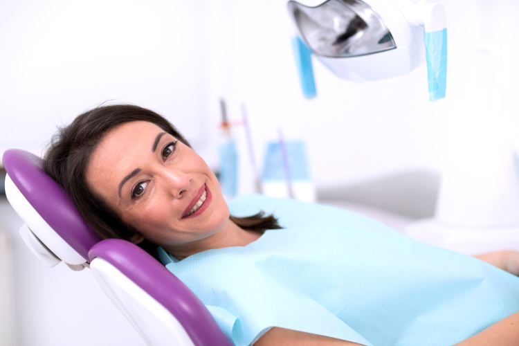 Smiling brunette woman in dental chair awaiting root canal therapy