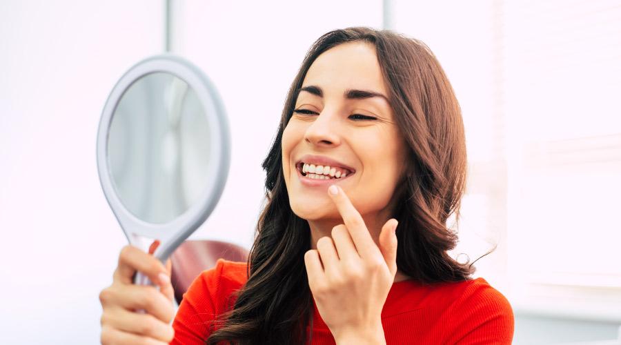 Smiling brunette woman admiring her dental veneers in a hand held mirror