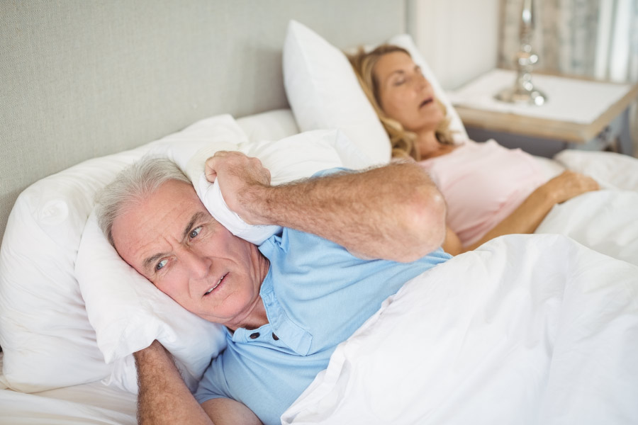 Man covering his ears with the pillow while his wife snores due to sleep apnea